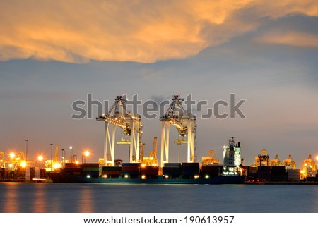 Container Cargo freight ship with working crane bridge in shipyard at dusk.