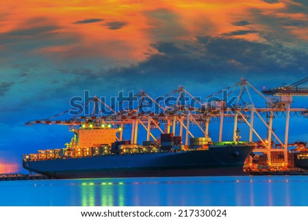 Container Cargo freight ship with working crane bridge in shipyard at dusk - stock photo