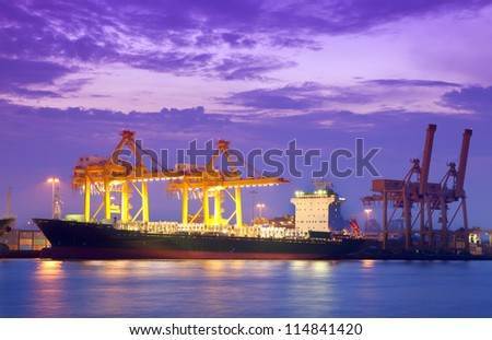 Container Cargo freight ship with working crane bridge in shipyard at dusk for Logistic Import Export - stock photo