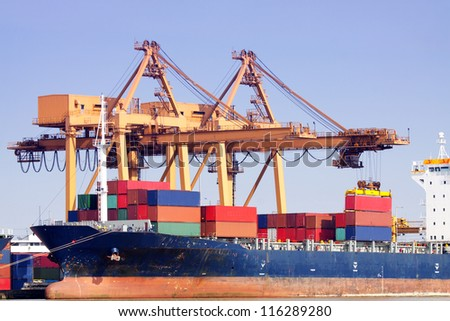 Container Cargo freight ship with working crane bridge in shipyard at dusk for Logistic Import Export background with blue sky - stock photo
