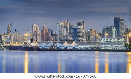 Container Cargo freight ship with working crane bridge in shipyard at dusk for Logistic Import Export background and Bangkok city background. - stock photo