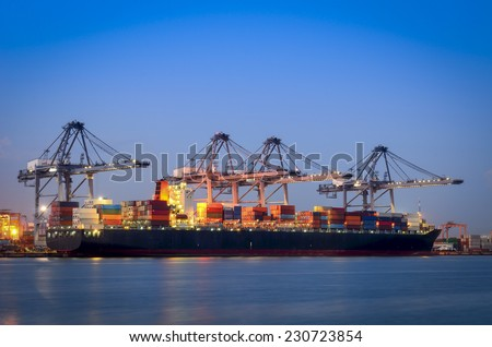 Container Cargo freight ship with working crane bridge in shipyard at dusk for Logistic Import Export at twilight - stock photo