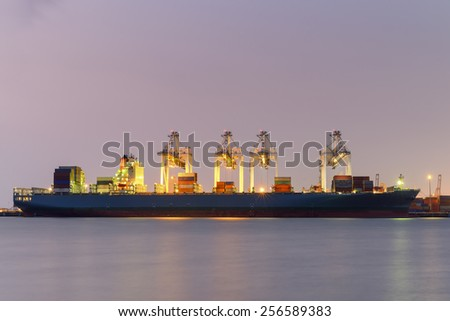 Container Cargo freight ship with working crane bridge in shipyard at dusk for Logistic Import Export at twilight