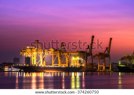 Container Cargo freight ship with working crane bridge in shipyard at twilight for Logistic Import Export background - stock photo