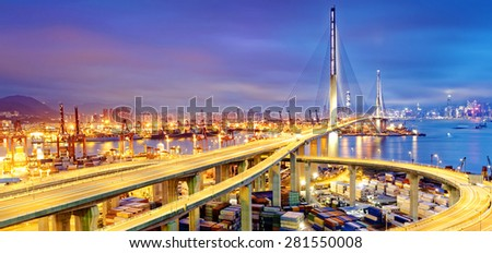 Container Cargo freight ship with working crane bridge in shipyard under Stonecutters highway bridge at sunset for Logistic Import Export, Hong kong - stock photo