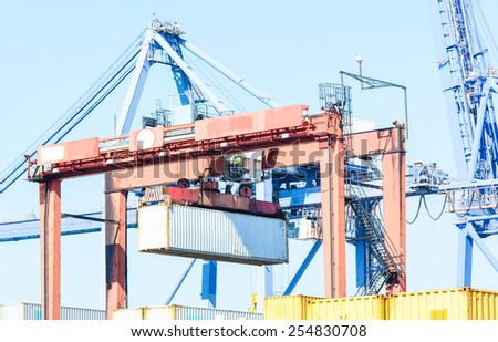 Container Cargo freight ship with working crane loading bridge in shipyard  - stock photo