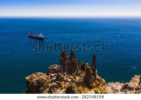 Container cargo ship and vessel on horizon in the blue ocean. View from above from rock or mountain - stock photo