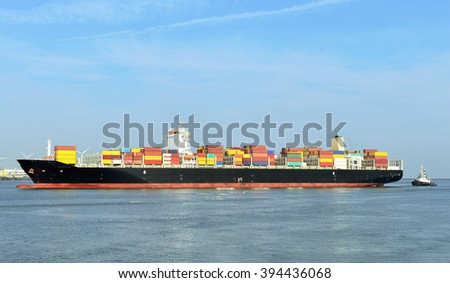 container cargo ship with tugboats in harbor