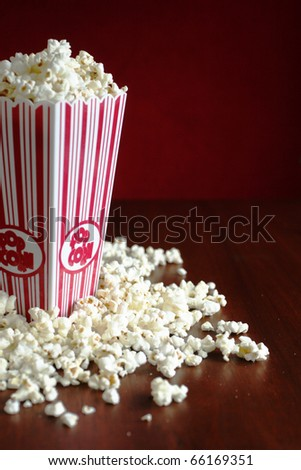 Container full of pop corn and few on a table - stock photo