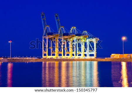 Container port terminal with cranes at sunset, sunrise, dawn time in Vancouver, Canada . Vertical.