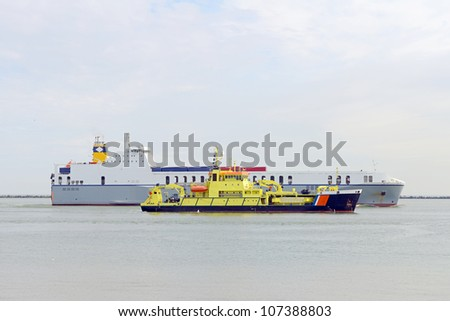 container ship and coast guard boat