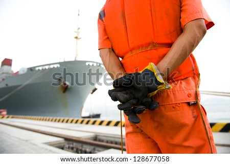 Container ship being unloaded with harbor dock worker standing besides it. - stock photo