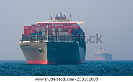 Container ship Hamber Bridge and tanker Nordbay anchored in the roads. Nakhodka Bay. East (Japan) Sea. 19.04.2014 - stock photo