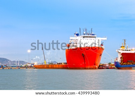 Container ship in import,export port against light of loading ship yard use for freight and cargo shipping vessel transport industry sea water down beach access - stock photo