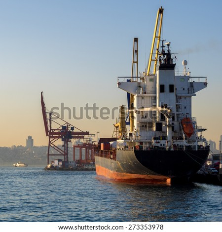 Container ship in sea port at sunset. Industrial landscape - logistic terminal, cargo ships and port cranes. - stock photo