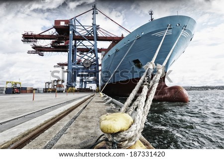 container ship mired in industrial port - stock photo