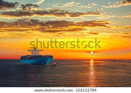 Container ship on sea road during sunrise. - stock photo