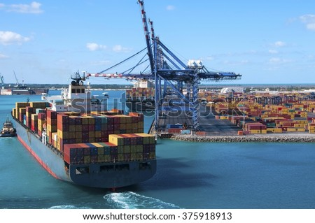 Container shipyard with heavy lifting Cranes and a ship coming in to dock assisted by tug boats