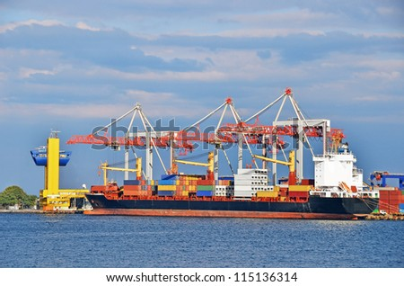 Container stack and ship under crane bridge - stock photo