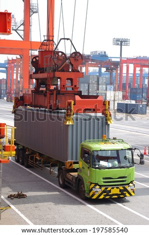 Container truck waiting for loading container box to Cargo ship - stock photo
