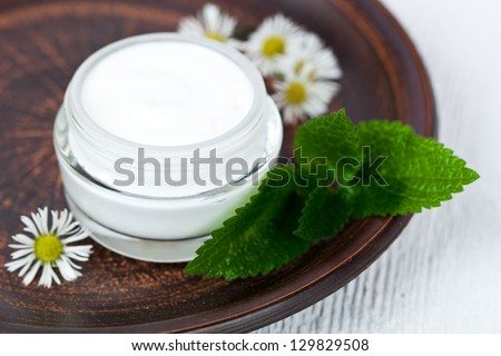container with cream urtica and chamomiles on browm plate - stock photo