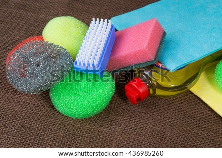Container with liquid for glass, wipes, colorful sponges for washing, blue cleaning brush - stock photo