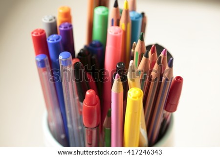 container with pens and pencils of various colors