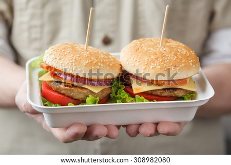 Container with two burgers in male hands