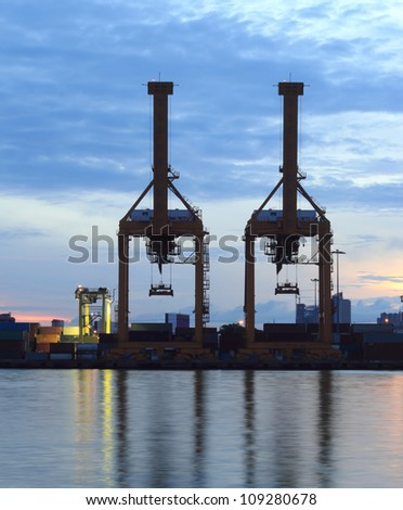 Containers and cranes at the port at sunrise in Bangkok, Thailand.