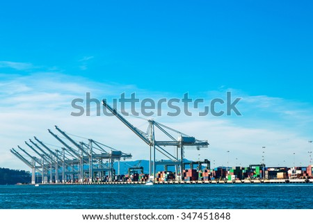 Containers and cranes in a harbor  - stock photo