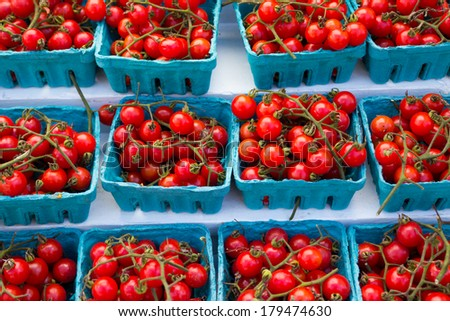Containers full of cherry tomatoes on display - stock photo