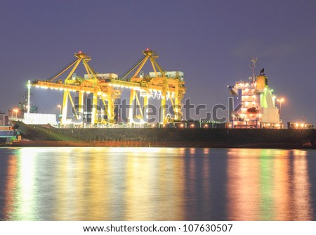 Containers loading at sea trading port at night