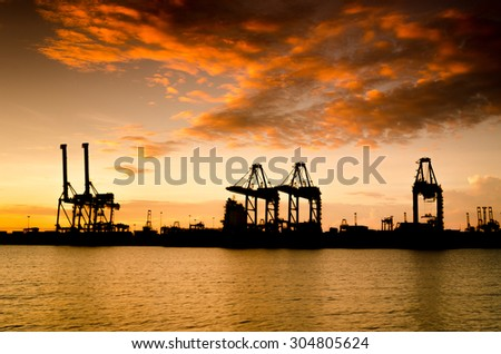 Containers loading by crane in Silhouette , Trade Port , Shipping , transport - stock photo