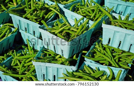 Containers of fresh green beans at a farmers market