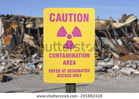 Contamination area warning sign with ruin background. - stock photo