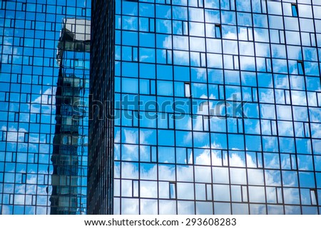 Contamporary glass facade with blue sky reflaction