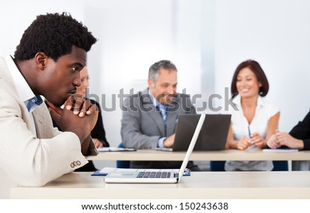 Contemplated African Businessman Looking At Laptop In Front Of Colleagues