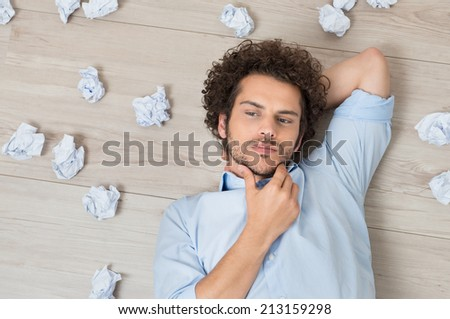 Contemplated Young Man Lying On Floor Surrounded With Crumpled Paper - stock photo