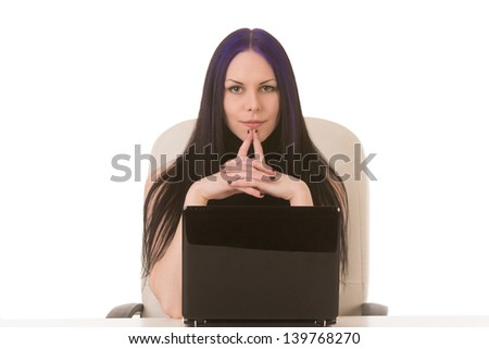 Contemplating business woman behind notebook, sitting at a desk - stock photo