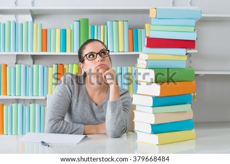 Contemplating Young Woman Sitting With Stack Of Books At Desk - stock photo