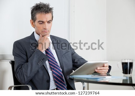 Contemplative mid adult businessman with hand on chin using digital tablet at desk in office - stock photo