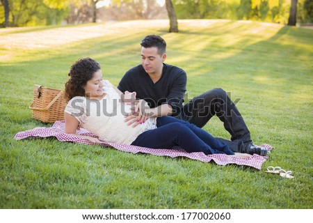 Contemplative Pregnant Hispanic Couple with Piggy Bank on Mother's Belly in the Park. - stock photo