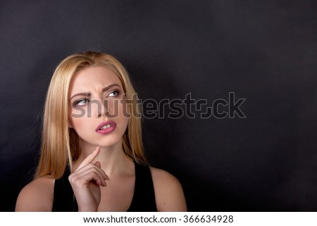 Contemplative thinking woman student at a black background - Stock Image - stock photo