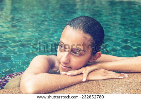 Contemplative young Asian woman in a sparkling blue swimming pool resting her head on her arms on the pool surround looking to the side with a pensive serious expression, close up of her face - stock photo