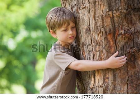 Contemplative young boy hugging a tree at the park
