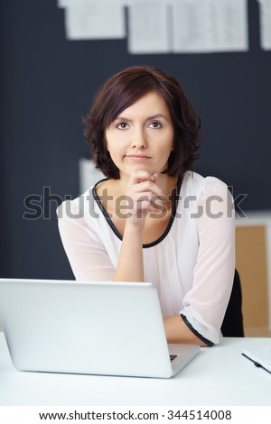 Contemplative Young Businesswoman Sitting at her Desk with Laptop Computer and Looking Away. - stock photo