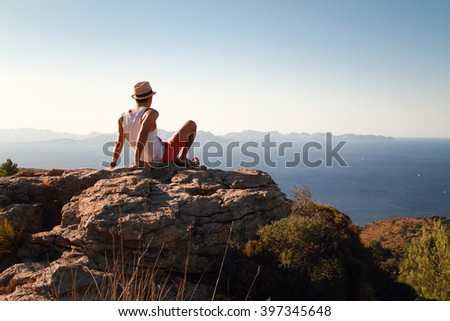Contemplative young man sitting on the rocks on the top of the mountain at sunset. Looking at distance with the blue sea in front. Wearing a straw at in summer. - stock photo