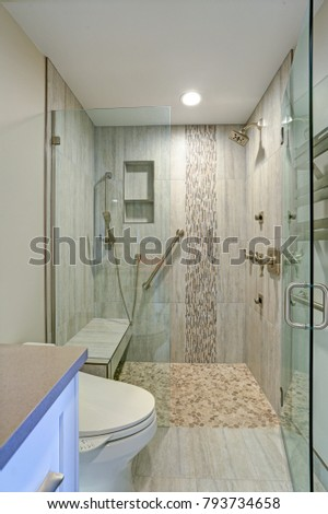 Contemporary bathroom design boasts gorgeous walk-in shower with tiled recessed shelves, built-in bench and accented with glass mosaic tiled vertical stripe.