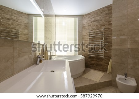 Contemporary bathroom in a luxury apartment. Expensive materials. Stone tile on walls and floor. White ceiling. White sanitary ware. Big window.