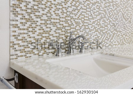 Contemporary bathroom sink with chrome fixtures, against a mosaic tile wall. - stock photo